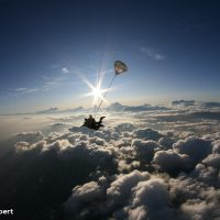 tandem skydiver in freefall with clouds