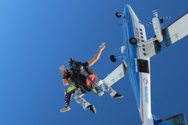 tandem skydiving student exiting plane
