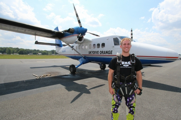tandem student stands in front of skydiving plane