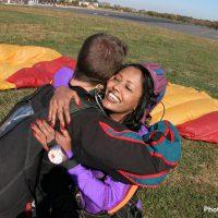 tandem skydiving student hugging instructor after landing