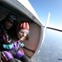 tandem skydiving student about to exit plane