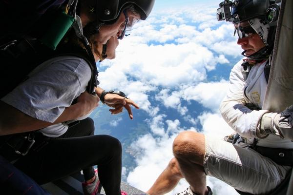 camera flyer prepares to capture tandem skydiving student