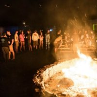 skydivers gather around bonfire at night