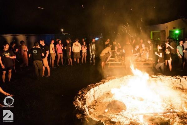 skydivers gather around bonfire at night