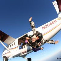 tandem skydiving instructor and student exiting airplane