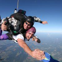 Skydive Orange tandem skydiver holding hand of videographer