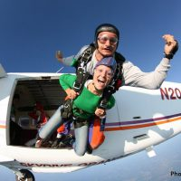 first time skydiver exiting plane with instructor