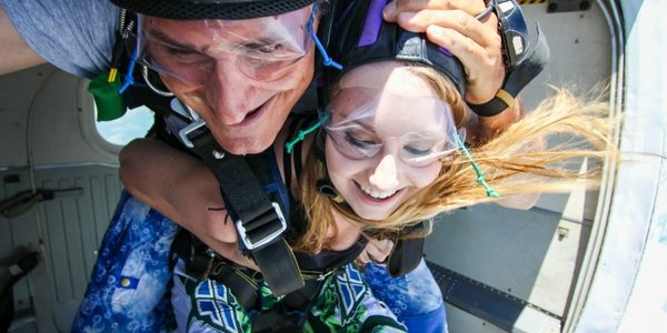 instructor makes sure tandem skydiving student is safe before exiting plane