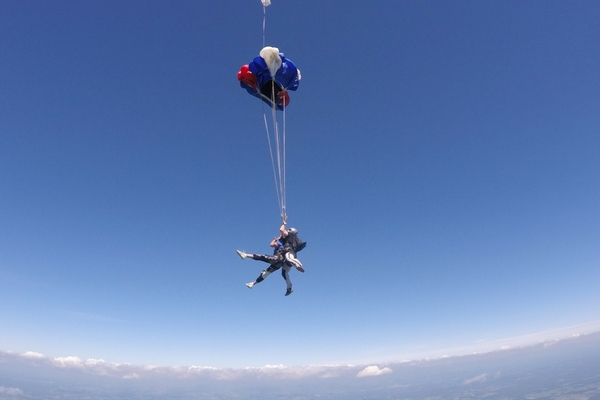 tandem skydiving instructor safely deploys parachute